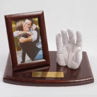Odlew dłoni młodzieńczej lub dorosłej osoby z ramką na zdjęcie.