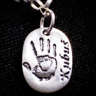 Mały owal z odbiciem dłoni dziecka w srebrze próby 999